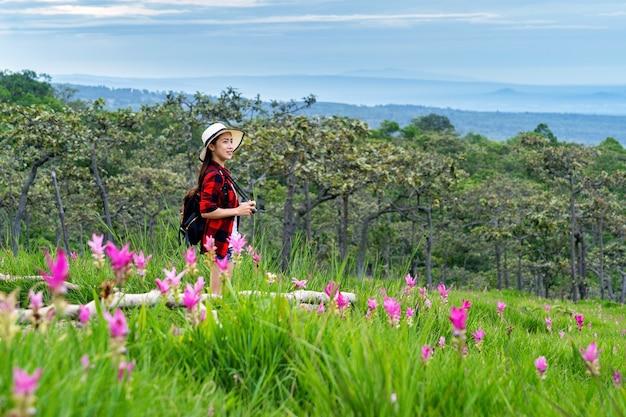 Viajero de mujer con mochila disfrutando en el campo de flores de krachiew, tailandia. concepto de viaje.