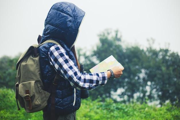 Viajero mujer con mochila con sombrero y mirando increíbles montañas y bosques.