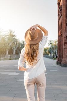 Viajero mujer de pie delante de un punto de referencia turístico popular con un sombrero y una camisa blanca