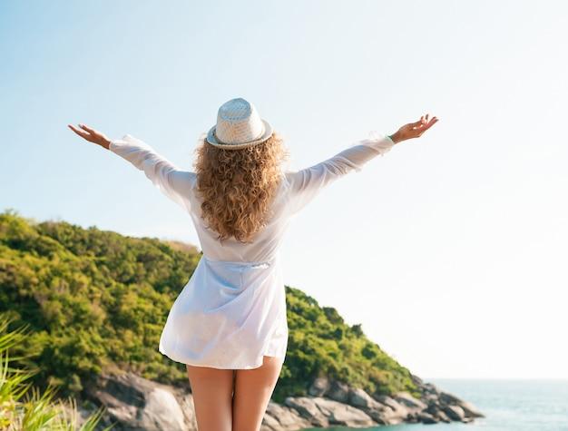 Viajero de mujer rizada posando con levantar los brazos en la playa en un día soleado