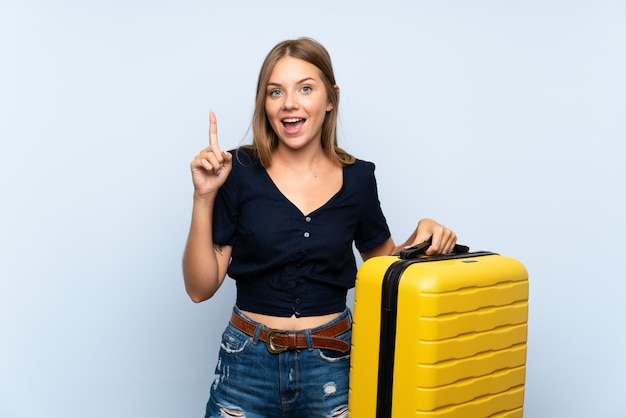Viajero mujer rubia con maleta apuntando hacia una gran idea