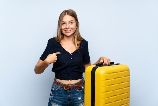 Viajero mujer rubia con maleta con expresión facial sorpresa