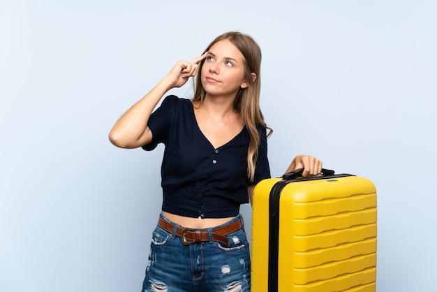 Viajero mujer rubia con maleta teniendo dudas y con expresión de la cara confusa