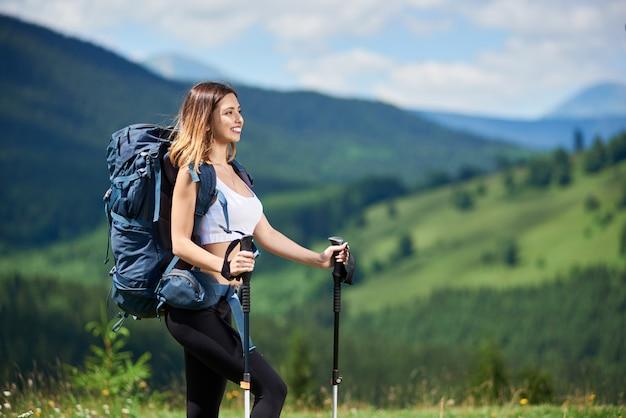 Viajero mujer senderismo en la cima de una colina