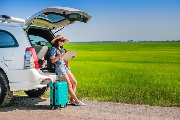 Viajero de mujer sentado en el portón de un auto y leyendo un mapa