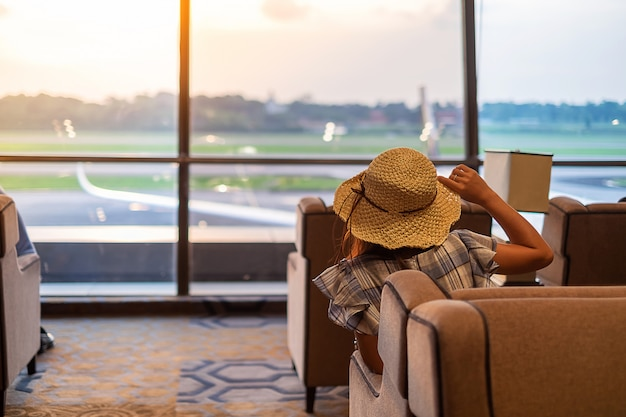 Viajero mujer con sombrero mirando a avión en la mañana amanecer