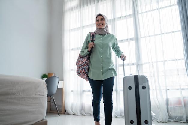 Viajero musulmán femenino llevando su bolso y sosteniendo la maleta
