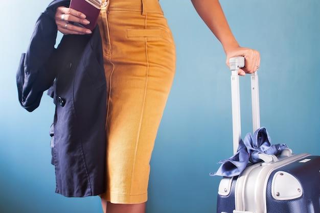Viajero de negocios, moda o mujer elegante que sostiene el equipaje en fondo azul