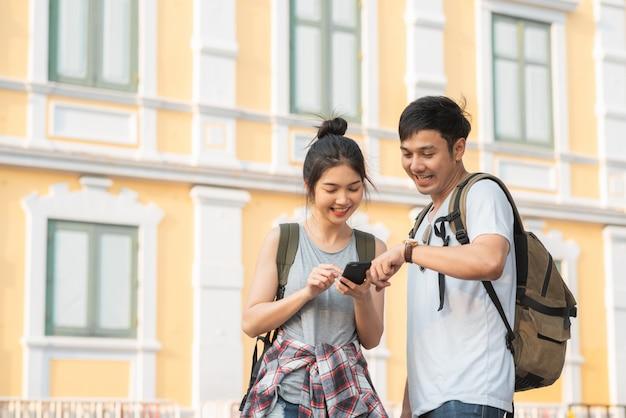 Viajero pareja asiática dirección en mapa de ubicación en bangkok, tailandia