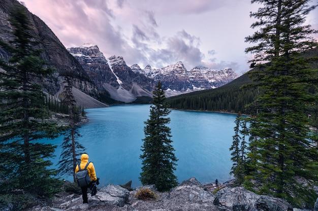 Viajero de pie en el lago moraine con montañas rocosas canadienses en el parque nacional banff