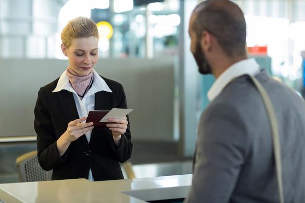 Viajero de pie en el mostrador mientras el asistente revisa su pasaporte