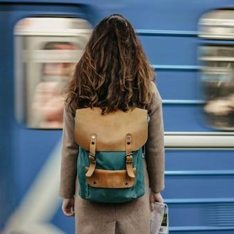 Viajero principal rojo rizado de la muchacha de la mujer joven con la mochila y el mapa en la estación de metro delante del tren