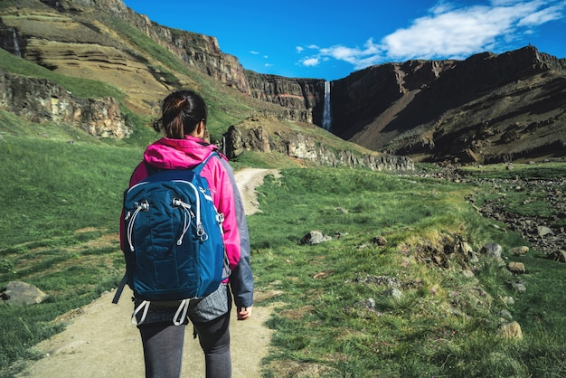 Viajero que camina en la cascada de hengifoss, islandia.