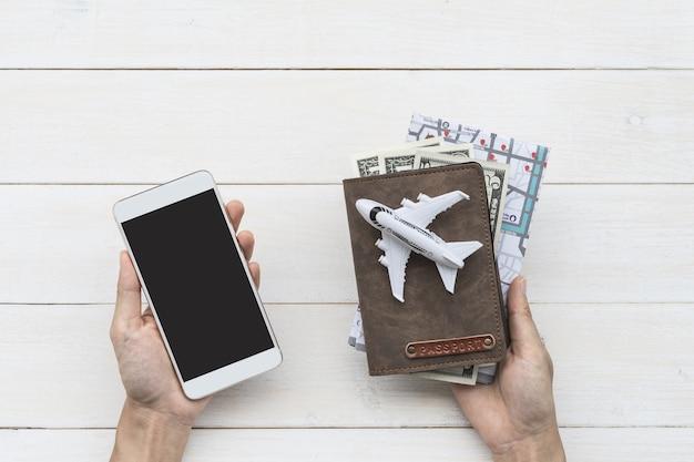 Viajero que sostiene el teléfono inteligente con pasaporte y mapa, concepto de viaje