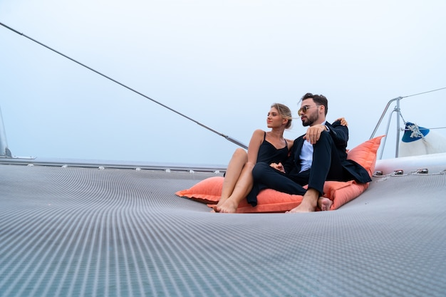 Viajero relajante pareja de lujo en bonito vestido y suite sentarse en puf en parte del yate de crucero con fondo de mar y cielo blanco. concepto de viaje de negocios.