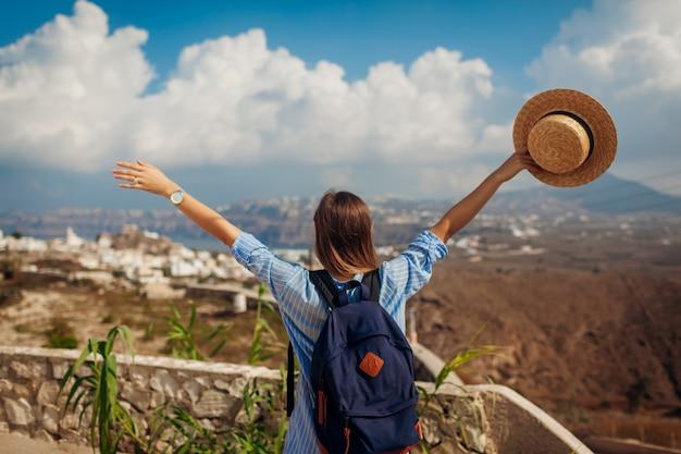 Viajero de santorini con mochila levantó los brazos sintiéndose feliz mirando a akrotiri, paisaje de montañas en la isla. turismo