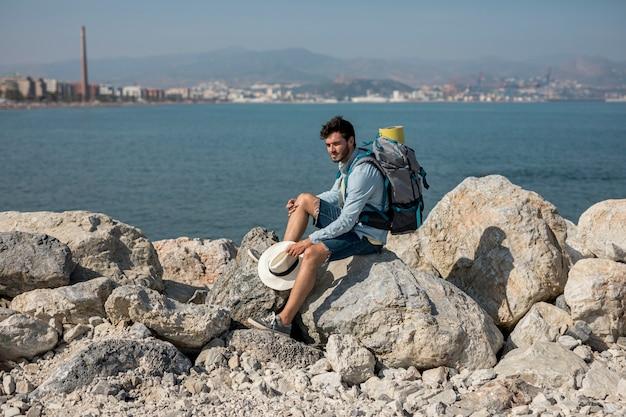 Viajero sentado en las rocas a la orilla del mar