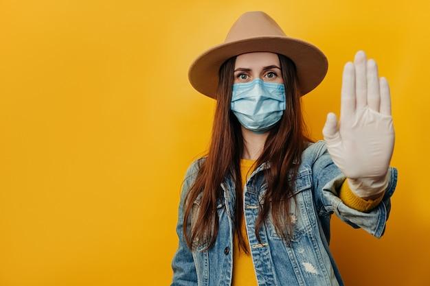 Viajero serio mujer turista en guantes médicos estériles mascarilla, mostrando gesto de parada, tratando de resolver el conflicto mientras coronavirus pandémico, aislado sobre fondo amarillo. concepto de cuarentena