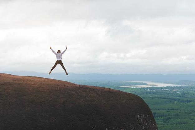 Viajero siente libertad saltar sobre fondo de naturaleza