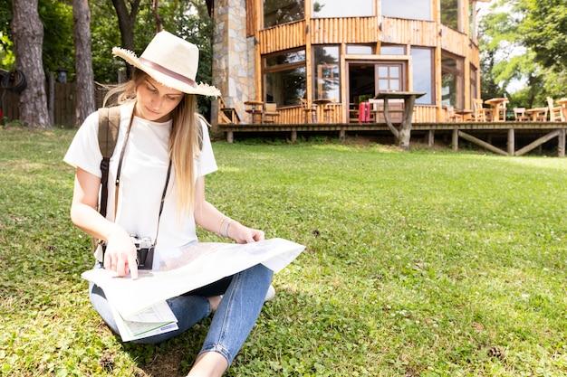Viajero sobre hierba mirando el mapa