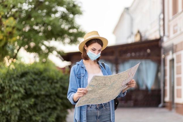 Viajero con sombrero y máscara médica comprobando el mapa