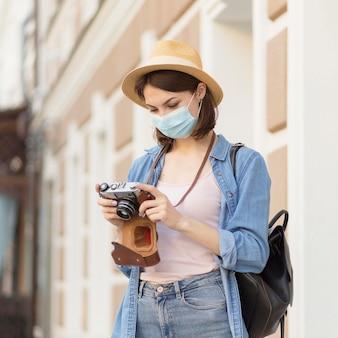 Viajero con sombrero y máscara médica revisando fotos