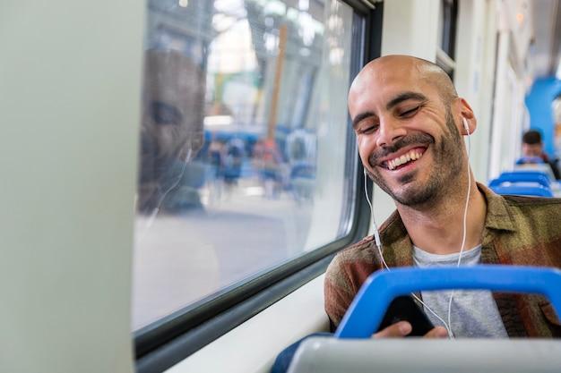 Viajero sonriente con auriculares en metro