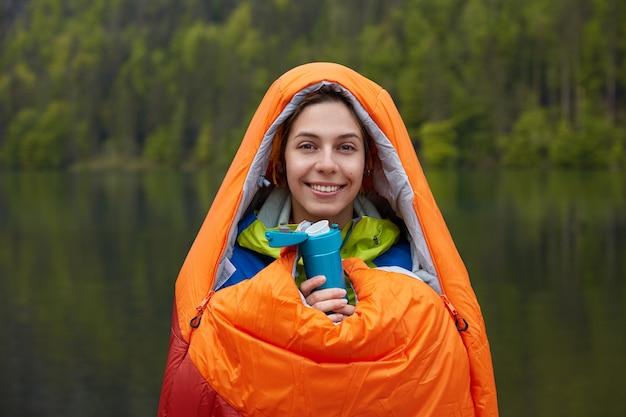 Viajero sonriente de buen humor, envuelto en un saco de dormir, pasa tiempo libre en la naturaleza, sostiene un termo de bebida caliente