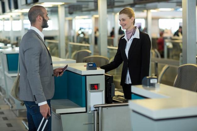 Viajero sonriente interactuando con el asistente en el mostrador de facturación