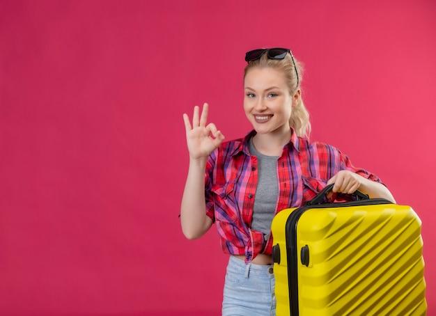 Viajero sonriente joven vestida con camisa roja sosteniendo la maleta muestra gesto oker sobre fondo rosa aislado