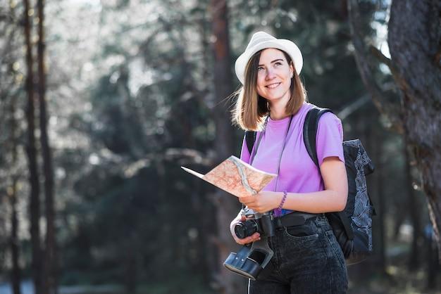 Viajero sonriente con mapa y cámara Foto gratis