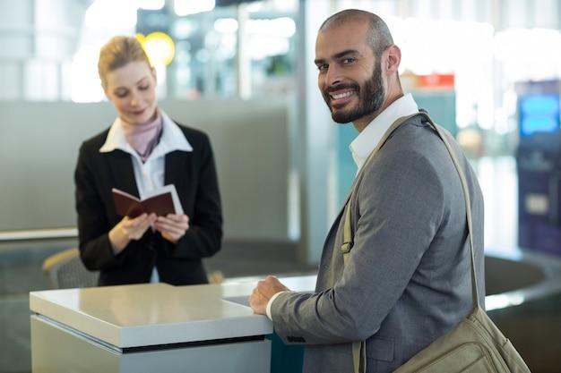 Viajero sonriente de pie en el mostrador mientras el asistente revisa su pasaporte