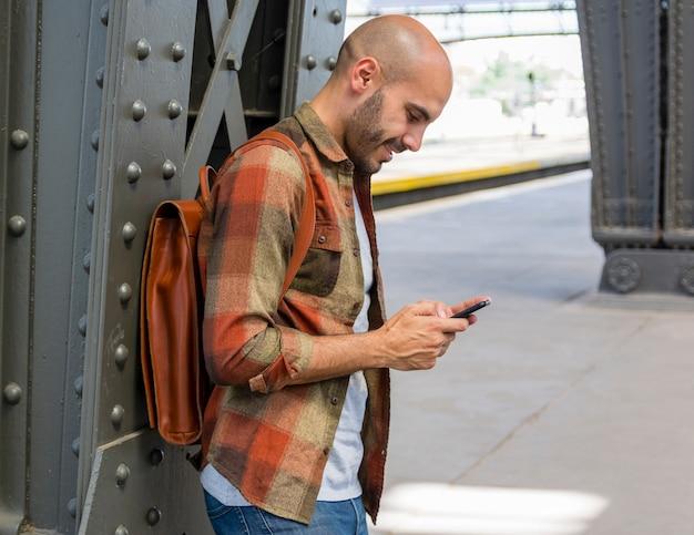 Viajero sonriente usando el móvil