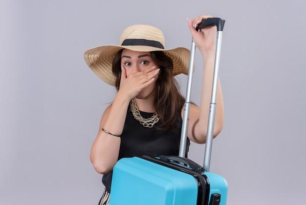 Viajero sorprendido joven vistiendo camiseta negra con sombrero sosteniendo la maleta y se cubrió la cara con la mano sobre fondo blanco.