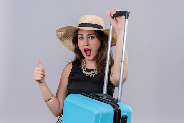 Viajero sorprendido joven vistiendo camiseta negra con sombrero sosteniendo maleta y su pulgar hacia arriba sobre fondo blanco.