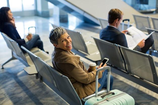 Viajero con taza de café mediante teléfono móvil en la zona de espera