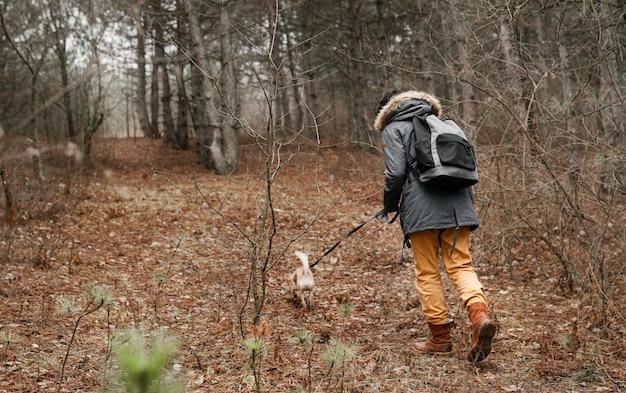 Viajero de tiro completo paseando a un perro en el bosque
