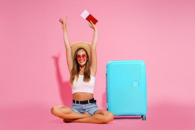 Viajero turista mujer con pasaporte y billetes maleta top blanco shorts sombrero de paja