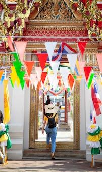 Viajero turístico mujer con sombrero entra en un templo budista en bangkok, viajando a asia