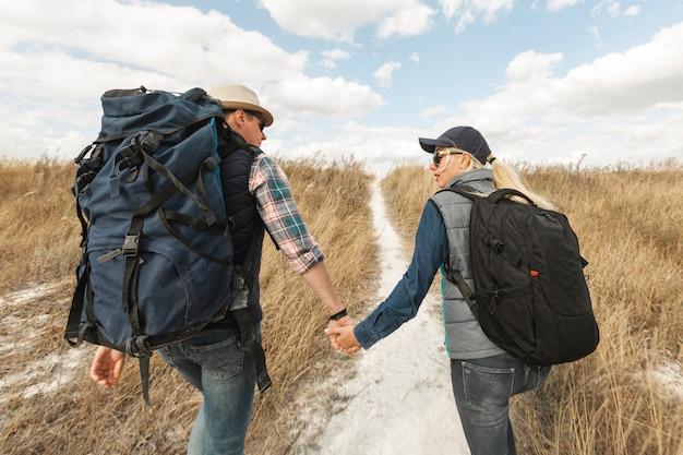 Viajeros adultos tomados de la mano al aire libre