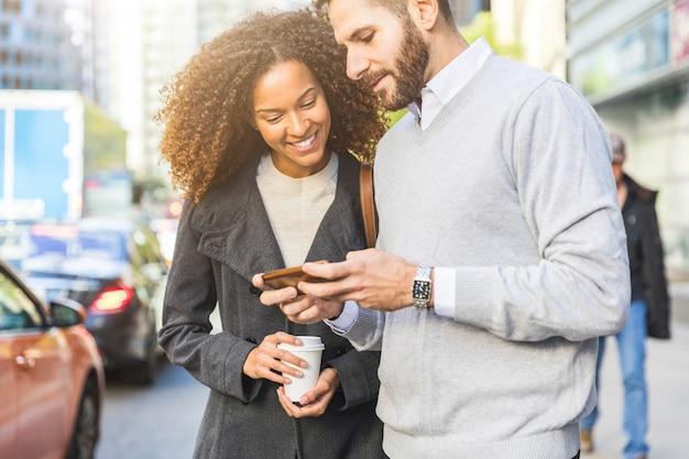 Viajeros en la ciudad, gente de negocios con un teléfono inteligente.