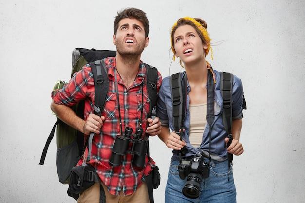 Viajeros descontentos con mochilas pesadas, binoculares y cámara, mirando hacia arriba mientras intentan comprender lo que está escrito en la señal de tráfico mientras se encuentran en un país extranjero. concepto de personas y turismo