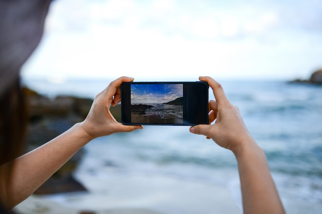 Los viajeros están tomando una foto del mar con un teléfono inteligente.