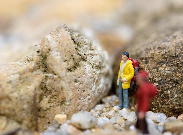 Viajeros de mochila en miniatura senderismo rock, concepto de viaje