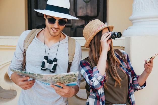 Viajeros perdidos con prismáticos, mapa y gafas de sol
