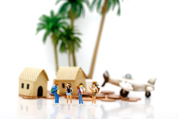Viajeros de pie con casas y aviones en monedas.