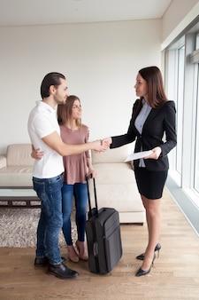 Viajeros que alquilan propiedades, pareja dándose la mano con agente inmobiliario.
