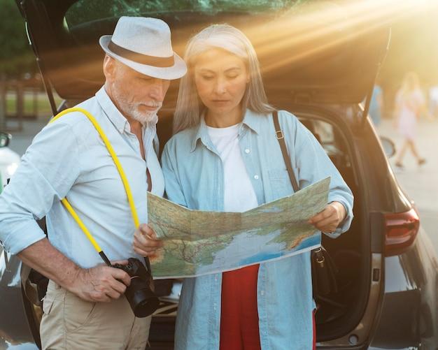 Viajeros senior de tiro medio con mapa