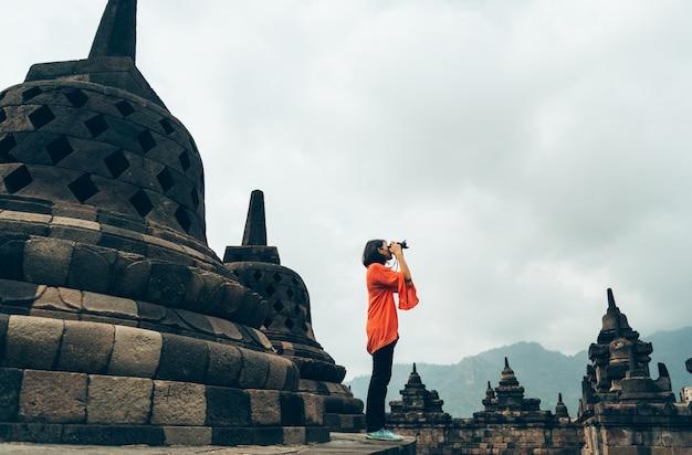 Los viajeros solitarios femeninos asiáticos toman los edificios antiguos de la foto en el templo de borobudur, java, indonesia