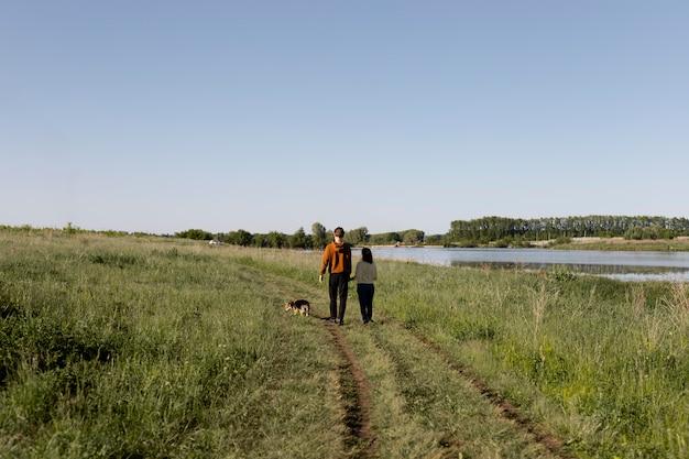 Viajeros de tiro largo con perro en la naturaleza
